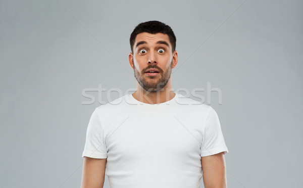 scared man in white t-shirt over gray background Stock photo © dolgachov