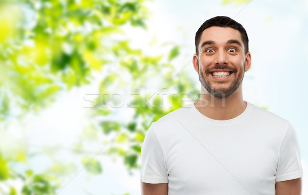 man with funny face over green natural background Stock photo © dolgachov