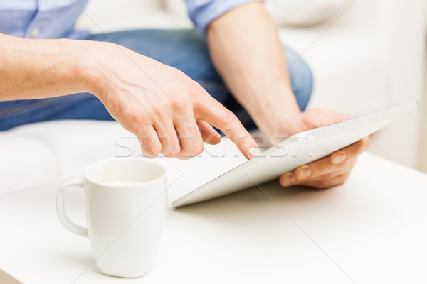close up of man with tablet pc and tea cup at home Stock photo © dolgachov