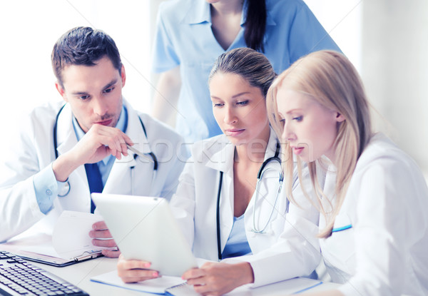 Stock photo: group of doctors looking at tablet pc