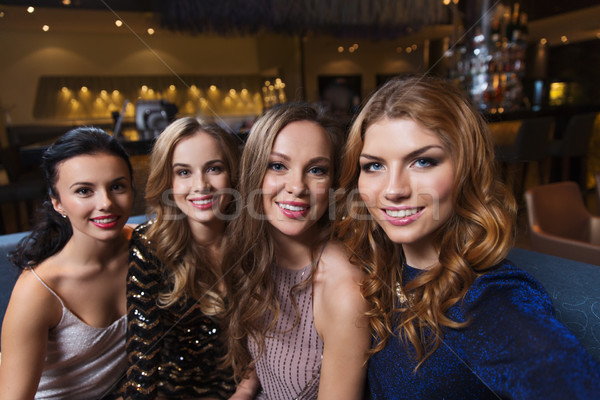 happy smiling women taking selfie at night club Stock photo © dolgachov