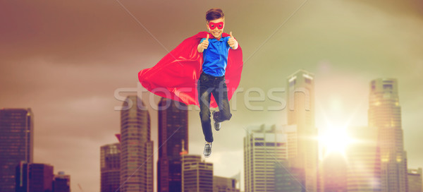 boy in superhero cape and mask showing thumbs up Stock photo © dolgachov