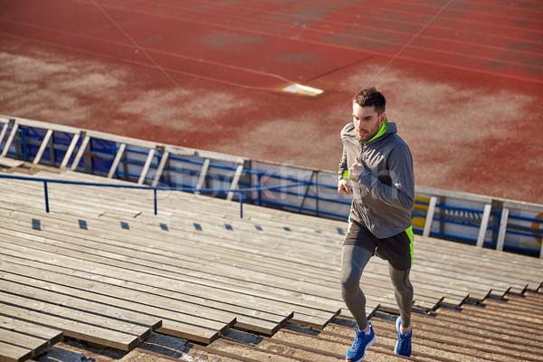 Jonge man lopen naar boven stadion fitness sport Stockfoto © dolgachov