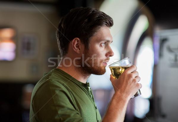 молодым человеком питьевой пива Бар Паб люди Сток-фото © dolgachov