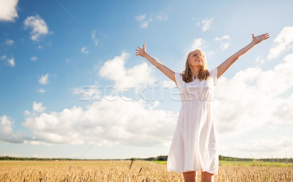 smiling young woman in white dress on cereal field Stock photo © dolgachov