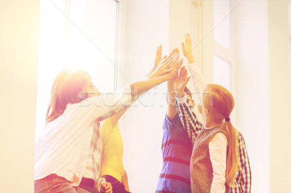 group of school kids making high five gesture Stock photo © dolgachov