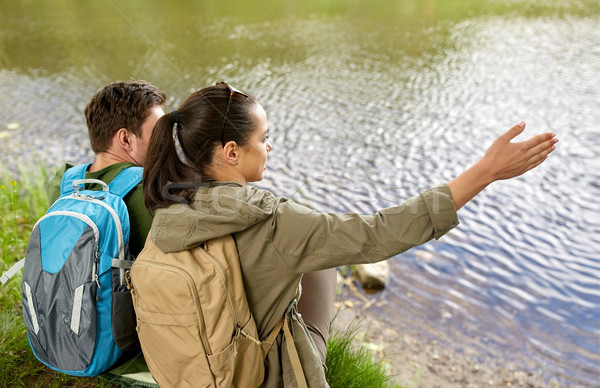 couple with backpacks sitting on river bank Stock photo © dolgachov