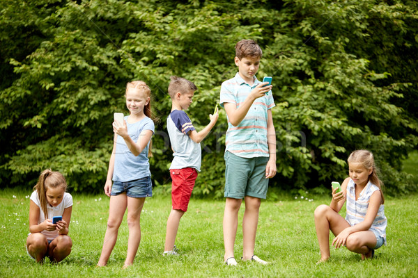 kids with smartphones playing game in summer park Stock photo © dolgachov