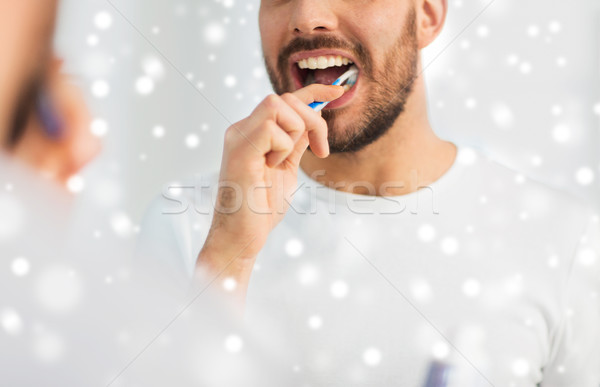 close up of man with toothbrush cleaning teeth Stock photo © dolgachov