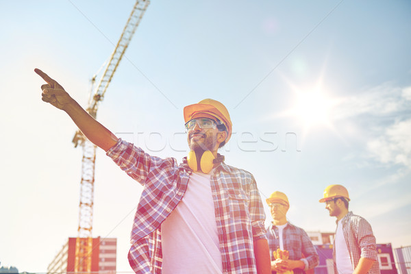 Stock photo: builders pointing finger aside on construction