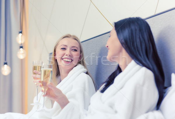 smiling girlfriends with champagne glasses in bed Stock photo © dolgachov