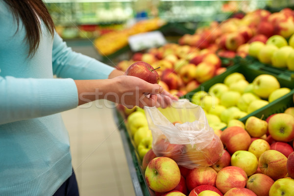 woman with bag buying apples at grocery store Stock photo © dolgachov