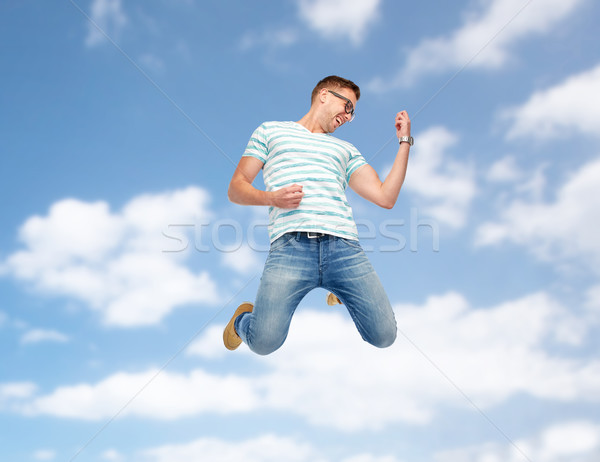 happy man jumping and playing imaginary guitar Stock photo © dolgachov