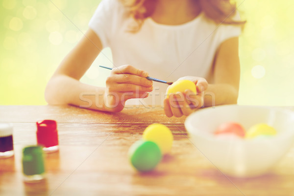 close up of girl with brush coloring easter eggs Stock photo © dolgachov