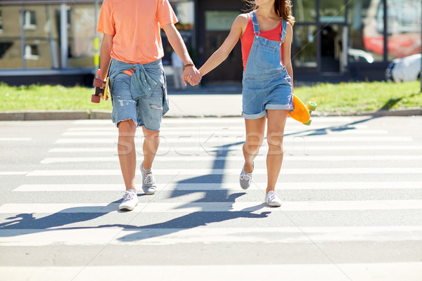 teenage couple with skateboards on city crosswalk Stock photo © dolgachov