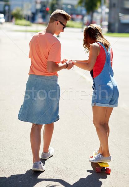 teenage couple riding skateboard on city street Stock photo © dolgachov