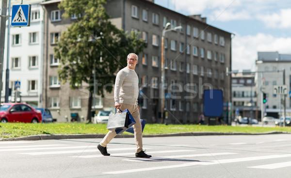senior man with shopping bags walking on crosswalk Stock photo © dolgachov