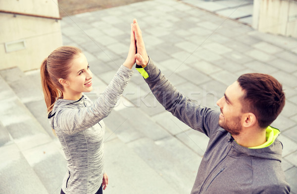 smiling couple making high five on city street Stock photo © dolgachov