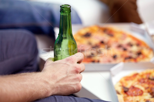 man with beer bottle and pizza at home Stock photo © dolgachov