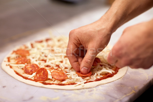 cook hands adding salami to pizza at pizzeria Stock photo © dolgachov