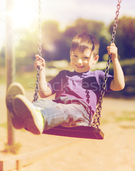happy little boy swinging on swing at playground Stock photo © dolgachov