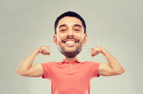 smiling man showing biceps over gray background Stock photo © dolgachov
