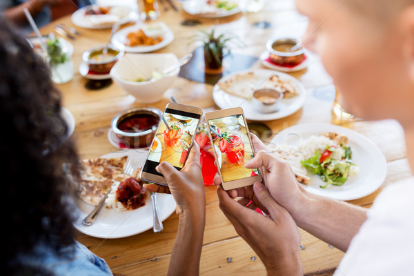 couple picturing drinks by smartphones at bar Stock photo © dolgachov