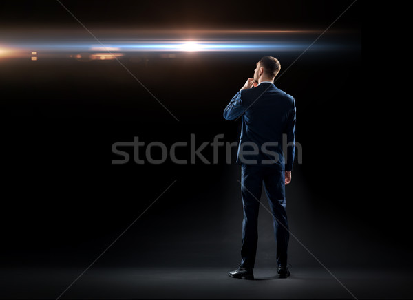 businessman over black looking at laser light Stock photo © dolgachov