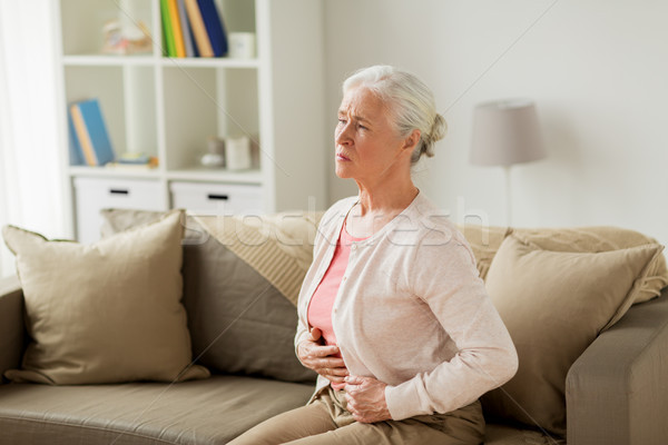 senior woman suffering from stomach ache at home Stock photo © dolgachov