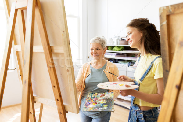 women with easels and palettes at art school Stock photo © dolgachov