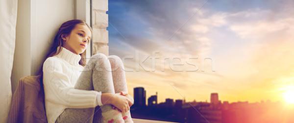 sad girl sitting on sill at home window Stock photo © dolgachov