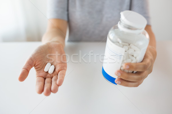 close up of hands holding medicine pills and jar Stock photo © dolgachov