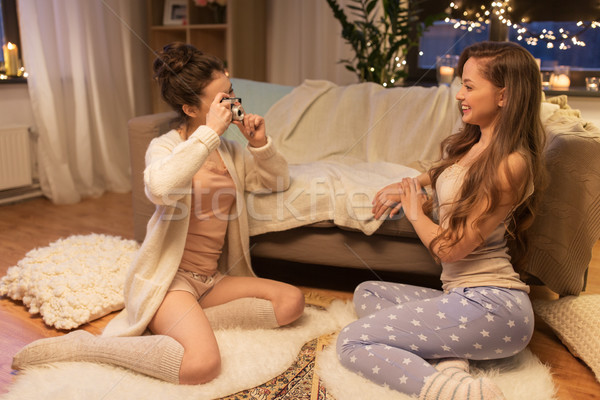female friends photographing by camera at home Stock photo © dolgachov