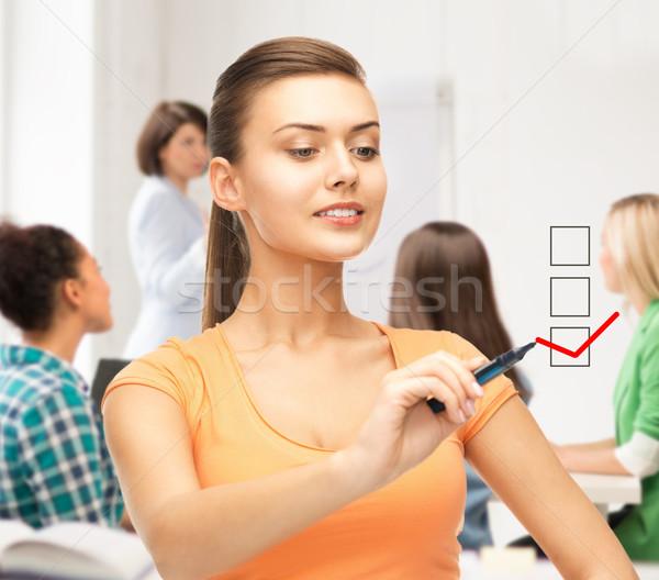 student drawing checkmark on virtual screen Stock photo © dolgachov
