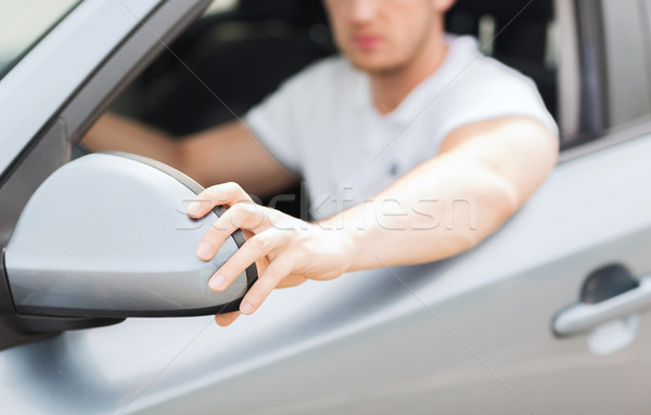 man ajusting rear view mirror Stock photo © dolgachov