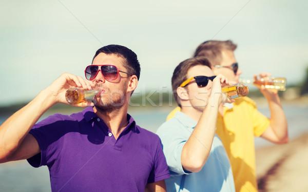 Barátok tengerpart üvegek ital nyár ünnepek Stock fotó © dolgachov