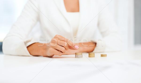 female hand putting euro coins into columns Stock photo © dolgachov