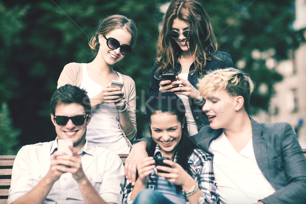 students looking at smartphones and tablet pc Stock photo © dolgachov