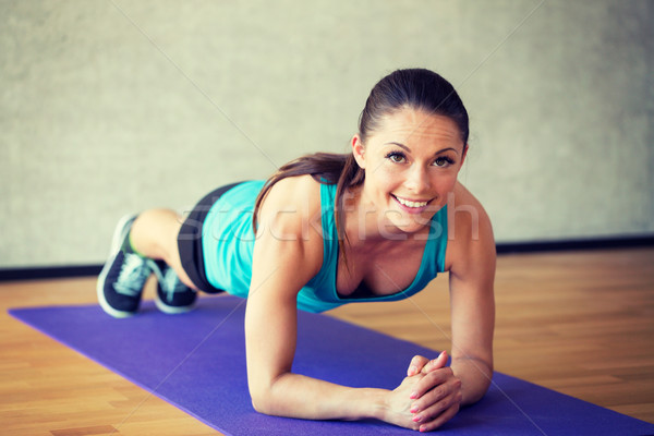 Stock photo: smiling woman doing exercises on mat in gym