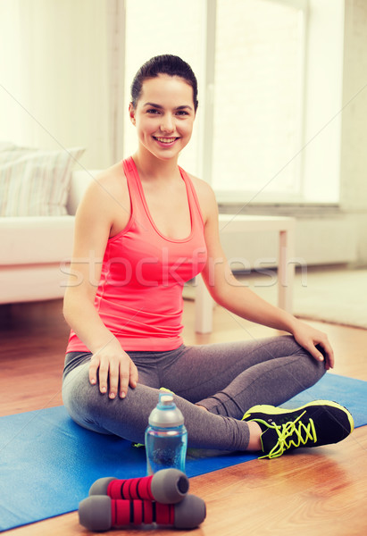 smiling girl with bottle of water after exercising Stock photo © dolgachov