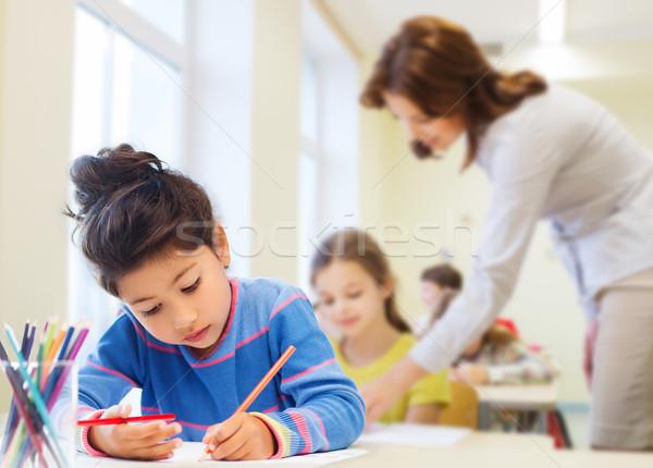 happy school girl drawing with coloring pencils Stock photo © dolgachov