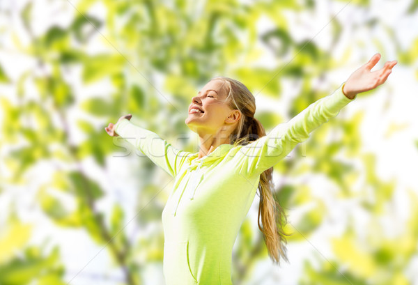 Stock photo: happy woman in sport clothes raising hands