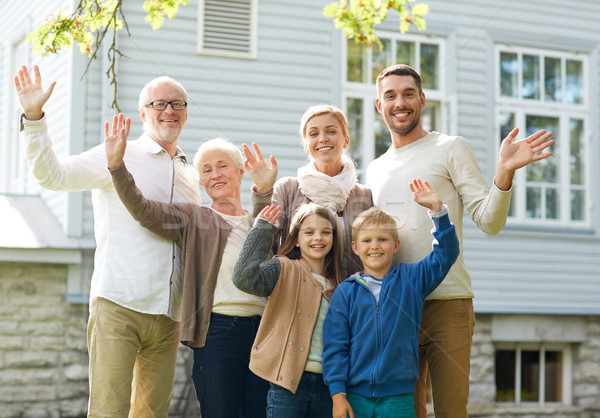 happy family waving hands in front of house Stock photo © dolgachov