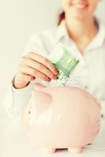 woman puts euro cash into large piggy bank Stock photo © dolgachov