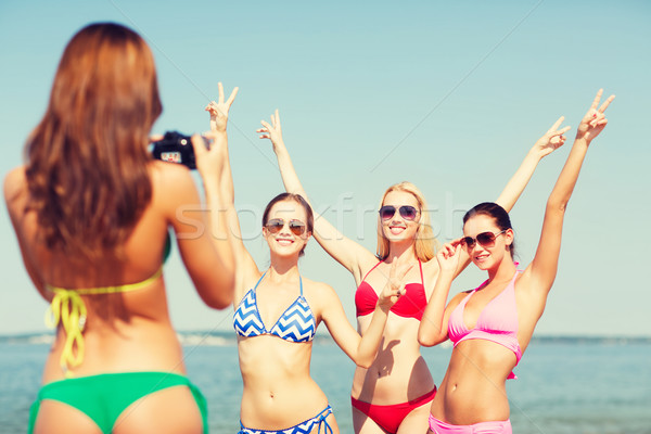 Stock photo: group of smiling women photographing on beach
