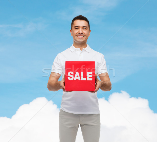 smiling man with red sale sigh over blue sky Stock photo © dolgachov