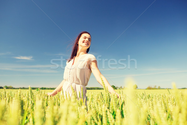Stock photo: smiling young woman on cereal field