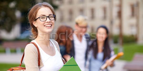 happy teenage students with school folders Stock photo © dolgachov