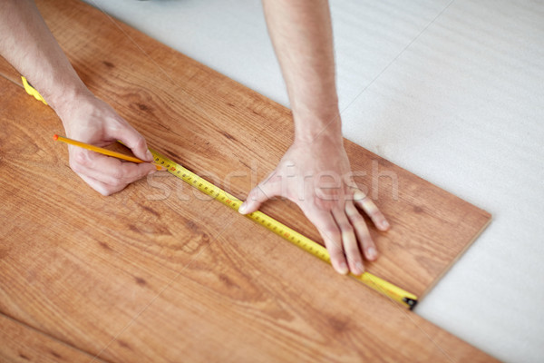 close up of male hands measuring flooring Stock photo © dolgachov