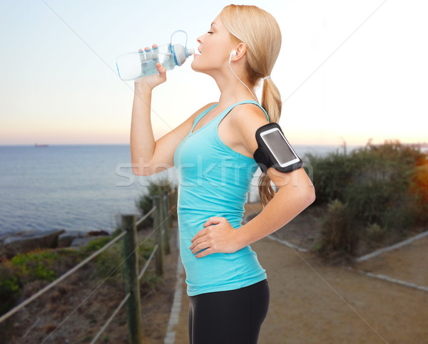 sports woman listening to music and drinking water Stock photo © dolgachov